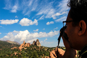 Close-up Of Man Photographing Rocky Mountains Against Sky At Colorado Springs