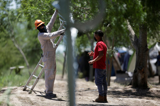 A migrant talks to an employee working on a fence placed around a migrant encampment, where more than 2,000 people live while seeking asylum in the U.S, as the spread of the coronavirus disease (COVID-19) continues, in Matamoros