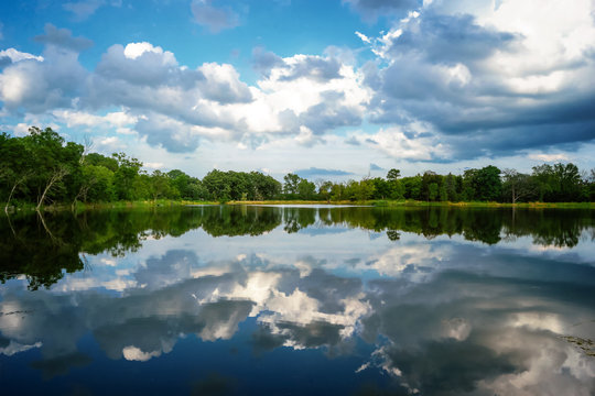 A lake view with the sky reflecting off the still surface at Independence Grove Forest Preserve in Libertyville, Illinois USA.