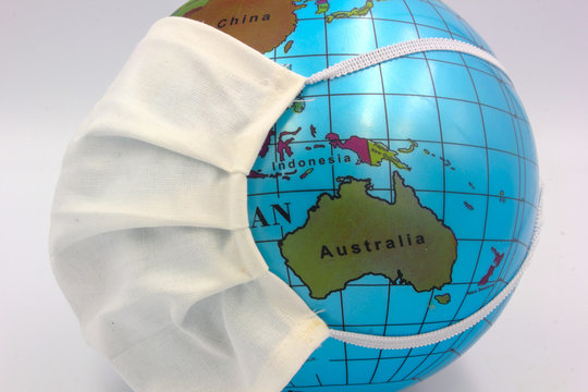 world earth globe focused on Australia and new Zealand with medical surgical face mask to combat corona virus covid 19