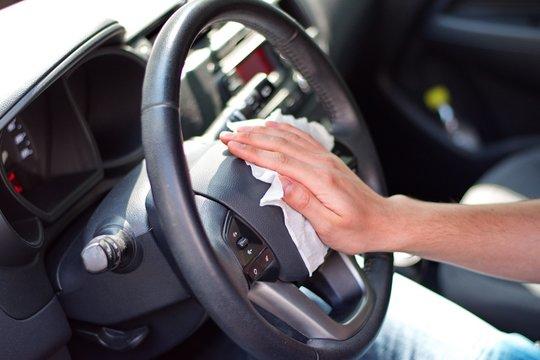 Man's hand cleaning steering wheel against virus with wet wipe