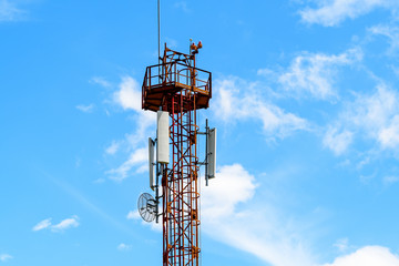 Telecommunications antennas on a red and white telecommunications tower with clear blue sky in the background