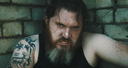 Portrait Of Angry Bearded Man Against Brick Wall
