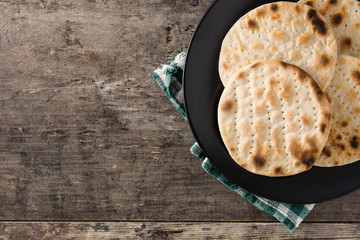 Handmade matzah for Jewish Passover in black plate on wooden table. Top view. Copy space