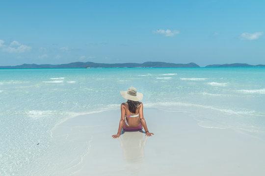 Woman on paradise blue beach. Tourist on Whitsundays beach, white sand, in pink bikini & hat, with aqua turquoise ocean. Travel, holiday, vacation, paradise, exotic. Whitsundays Islands, Australia.