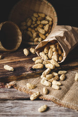 Close-up Of Peanuts In Paper Bag And Bowl At Table