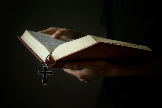 Midsection Of Woman Holding Bible With Cross Against Gray Background