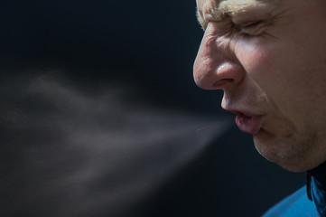 Mann niest vor schwarzem Hintergrund mit detaillierter Darstellung von ausgestoßenen Krankheitserregern