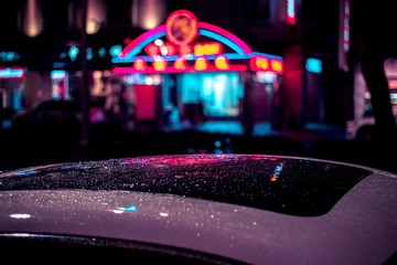 Selective focus shot of a wet roof of a car in a city with a blurry building in the background Fotobehang