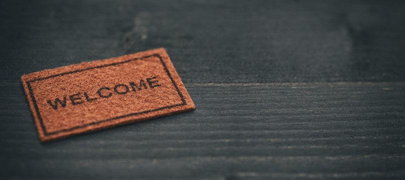 Old Welcome door mat on black wooden background