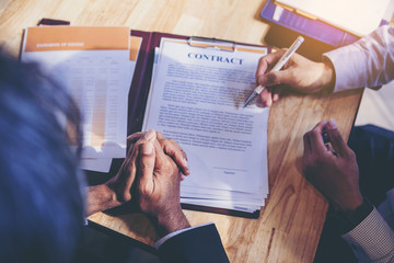 Businessman reading documents at meeting, business partner considering contract terms before signing checking legal contract law conditions