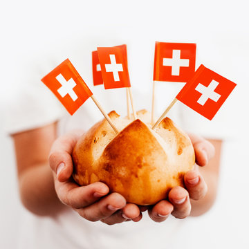 Traditional swiss bread buns in child hands with swiss flags on toothpicks. Square format.