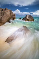 Wave splashing on a granite rock on the beach in Seychelles