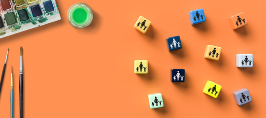 cubes with day care icons and water colors on orange background