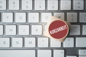 cube showing German message for SHORT TIME WORK on a computer keyboard
