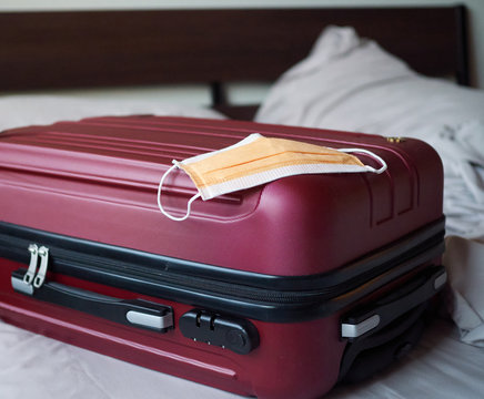 Closed red suitcase on the bed with facial mask on top ready to travel