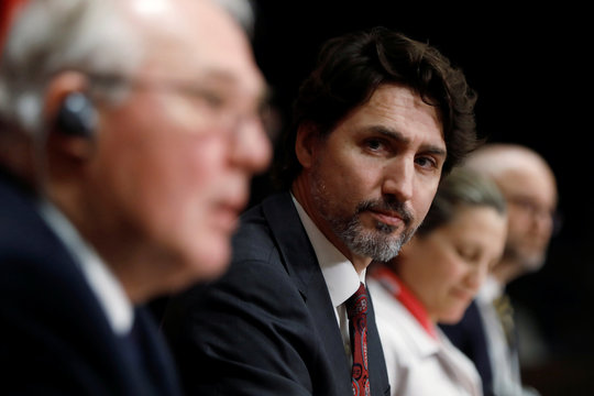 Canada's Prime Minister Justin Trudeau listens to Minister of Public Safety and Emergency Preparedness Bill Blair during a news conference on Parliament Hill in Ottawa