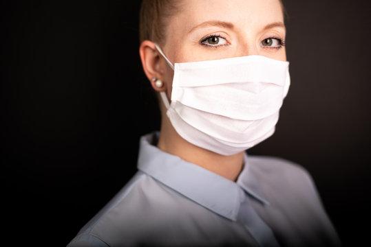 Junge Frau trägt Schutzmaske während Maskenpflicht vor schwarzen Hintergrund