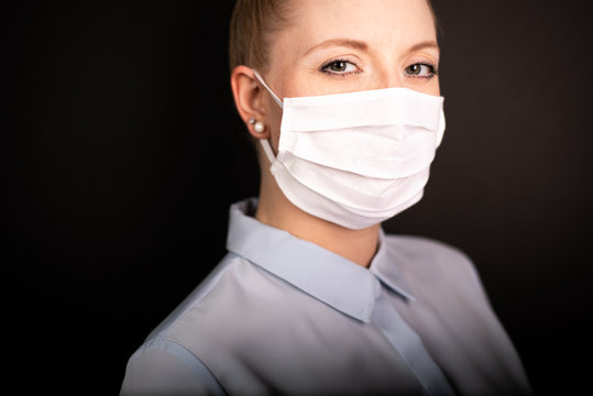 Young European woman wearing face mask to protect from COVID-19 isolated on black background
