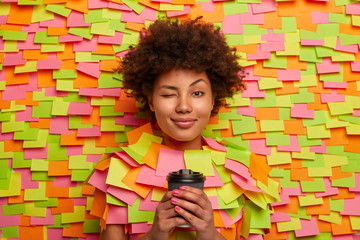 Sleepy African American woman winks eye, holds disposable cup of coffee, works for long hours, tries to be fresh, has natural curly hair, stick head through paper background, sticky notes around