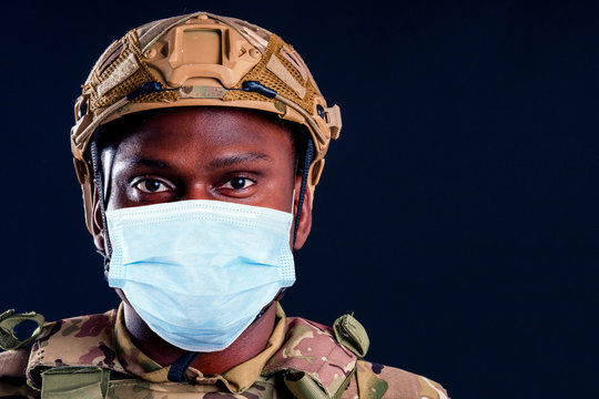 military army african male warrior camouflage suit sorrow sadness wrapped in an American flag black background studio, lying violence news criminal media