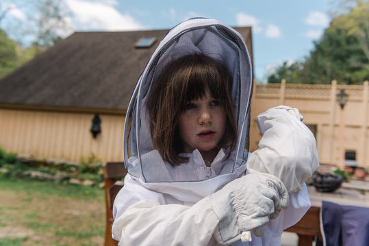 little girl getting dressed in apiarist suit to check on beehive