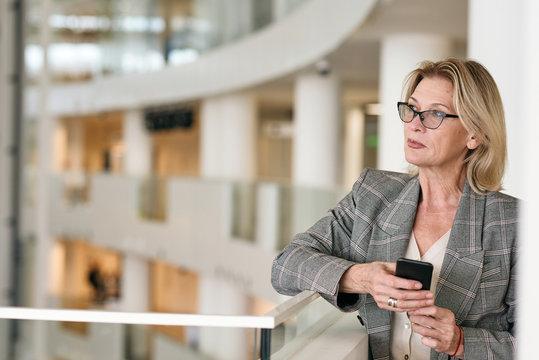 Pensive Senior Businesswoman With Smartphone