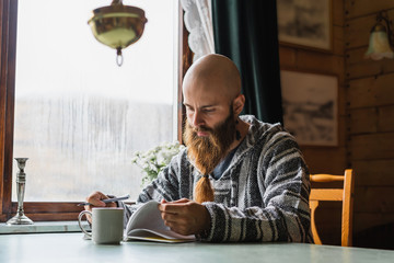 Thoughtful man making notes in diary Fotobehang