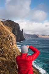 Anonymous traveler taking pictures of cliff and stormy sea