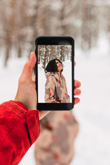Person using smartphone for taking photo of woman