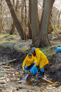 Woman and man in raincoats collecting plastic garbage