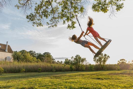 Cheerful girls swinging on swing