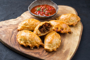 Traditional South American empanada de carne offered with a chili dip as closeup on a rustic wooden board