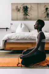 Young woman meditating in bedroom