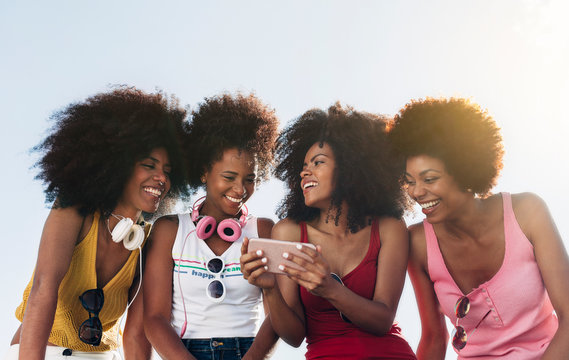 Afro women friends hanging out in the city using a cellphone