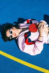 Female Teenager Lying on Blue Basketball Court