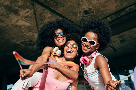 Afro women friends hanging out in the city waving LGBT