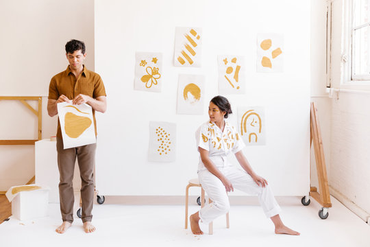 young man hanging paintings on wall while girl lounges in artist studio