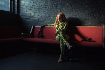 Drag queen holding shoes sitting on couch