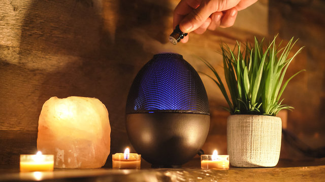 Woman adding essential oil to electric diffuser lamp, Aromatherapy