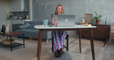Comfortable work from home on lockdown. Young cheerful business woman in pajamas pants using laptop...