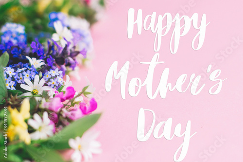 Happy Mother's day text, greeting card. Colorful spring flowers border on pink background with greeting sign. Floral greeting card. Happy Mothers day concept