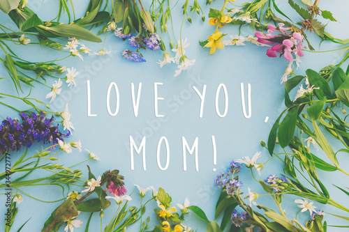 Love you Mom! Happy Mother's day greeting card. Heart of colorful spring flowers on blue background flat lay with greeting text. Floral greeting card. Happy Mothers day stylish flat lay