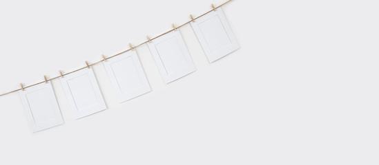 Mock-up marcos de fotos blancos de papel colgados con pinzas de madera