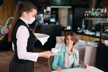 A European-looking waiter in a medical mask serves coffee.