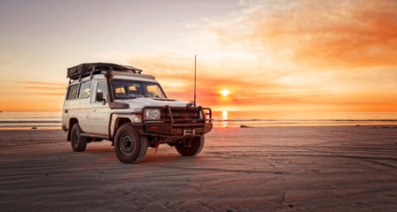 Foto op Plexiglas Cappuccino Outback relaxing adventure with 4WD vehicle at the beach of an ocean at sunrise