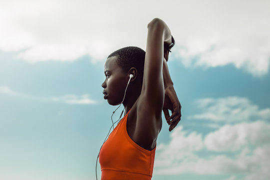 African woman with earphones doing stretching exercise