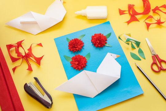 DIY instructions. How to make card with carnation flowers and origami dove at home. Step 10. Cut out the green paper leaves for cloves and place the details of the card on the blue cardboard