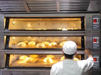 Zelfklevend Fotobehang Brood Male baker putting bread into the oven