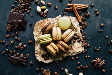 Macarons saveur vanille chocolat pistache et café avec des morceaux de chocolat des pistaches des batons de cannelle et des pistaches sur le fond noir